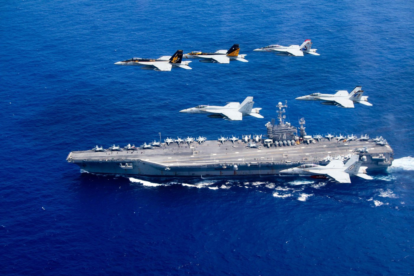 """A combined formation of aircraft from Carrier Air Wing (CVW) 5 and Carrier Air Wing (CVW) 9 pass in formation above the Nimitz-class aircraft carrier USS John C. Stennis (CVN 74) in the Philippine Sea, July 17, 2016.  The formation included F/A-18 Hornets from the """"Black Aces"""" of Strike Fighter Squadron (VFA) 41, the """"Diamondbacks"""" of Strike Fighter Squadron (VFA) 102, the """"Eagles"""" of Strike Fighter Squadron (VFA) 115, the """"Royal Maces"""" of Strike Fighter Squadron (VFA) 27, the """"Vigilantes"""" of Strike Fighter Squadron (VFA) 151, and the """"Warhawks"""" of Strike Fighter Squadron (VFA) 97. The Nimitz-class aircraft carriers USS John C. Stennis and USS Ronald Reagan (CVN 76) conduct dual aircraft carrier strike group operations in the U.S. 7th Fleet area of operations in support of security and stability in the Indo-Asia-Pacific. The operations mark the U.S. Navy's continued presence throughout the area of responsibility. (U.S. Navy photo by Lt. Steve Smith / Released)"""